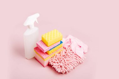 Cleaning spray, sponges, microfiber cloth and gloves on pink background