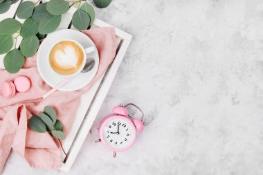 Cup of coffee on white wooden serving tray with alarm clock and eucalyptus branch. Flat lay, top vie