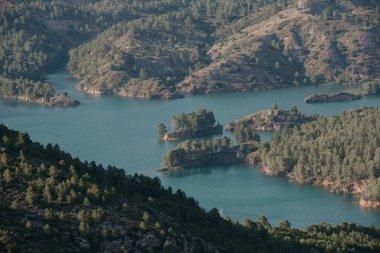 """Картина, постер, плакат, фотообои """"изумрудное озеро с маленькими островами в центре долины, покрытое лесом вечером в испании природа"""", артикул 205609460"""