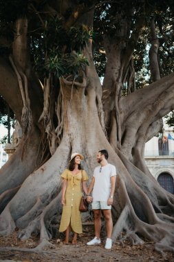 Beautiful young brunette woman with her boyfriend with beard standing under the giant tree in Spain in the evening