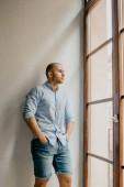 Luomo abbronzato brutale nella camicia blu e blue jeans shorts misses che tengono le mani nelle tasche dellappartamento con le pareti bianche vicino alla finestra in Spagna