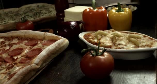 Čtvercová italská pepperoni a sýrová pizza, domácí recept, se ingrediencemi, pizza obklopená čerstvými ingrediencemi v kuchyni, na dřevěném stole
