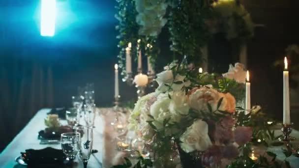 stůl s černými šipkami s jídlem, vinné sklenice, vázy, svícny se svíčkami uprostřed kouř a světlo