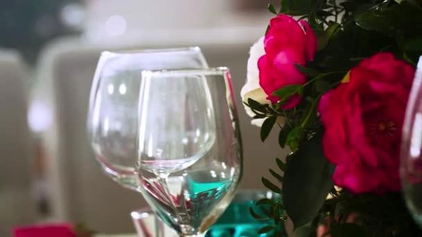 několik sklenic na víno uprostřed sklenice a talíře a květinové ujednání