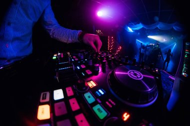 DJ plays on music mixer in a nightclub