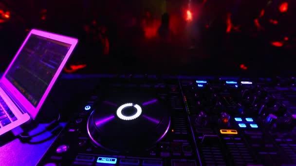 rozmazané tančící davy lidí v nočním klubu na večírku s hudebním mixérem DJ