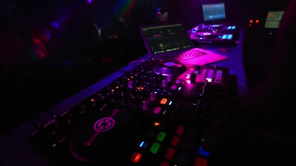 DJ hands mixing music in a nightclub on a mixer controller