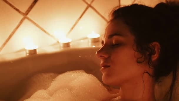 beautiful brunette lying in the bathroom with foam. Romantic setting with candles