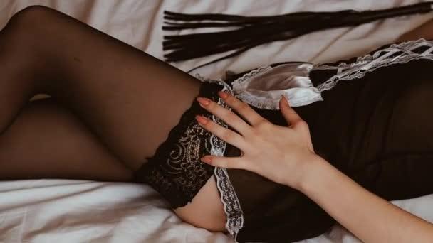 Sexy mladá dívka v kostýmech u služky leží na posteli vedle koženého biče a kouše jí zadek na zadku a štíhlé tělo