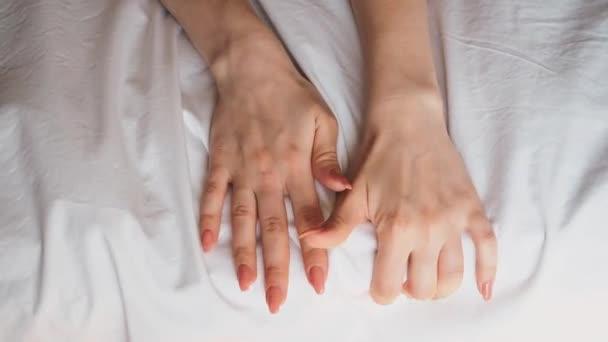 Hände eines jungen Paares Liebhaber Sex Intimität ziehen weiße Laken in Ekstase auf dem Bett, Orgasmus