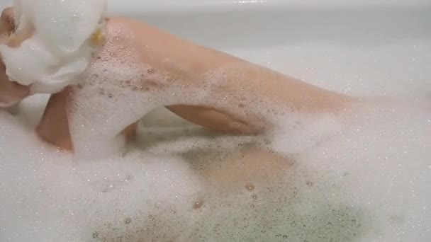 Krásná brunetka sexuálně pohladila svou nohu a zpívá v koupelně s pěnou