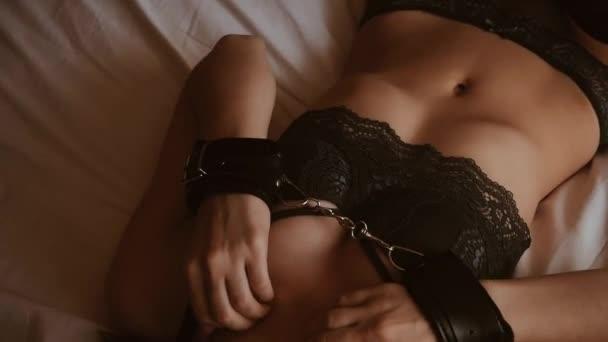 Szexi fiatal lány megbilincselték kezek megérinti érzékien és szexuálisan simogatja mellek egy melltartó