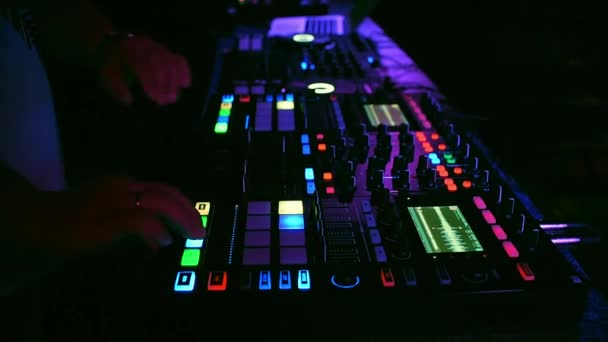 DJ mixes music on a professional mixer controller in a nightclub