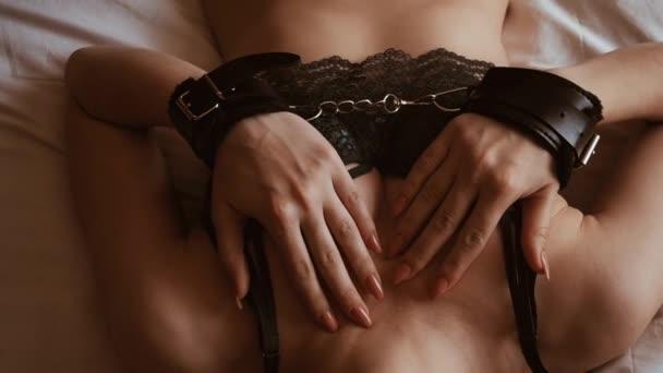 Sexy mladá dívka s spoutané rukou se smyslně a sexuálně polaská její prsa v podprsence