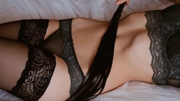 Sexy mladá dívka ve spodní prádlo smyslně drží kožený bič Flogger na jejím těle. Koncepce nadvlády a podávání s sexuálními hračkami