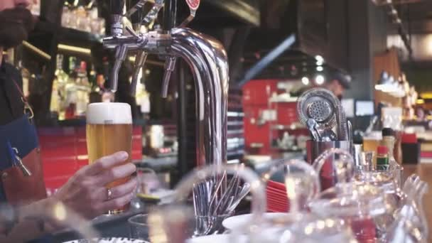 Versando birra fresca. Primo piano del giovane barista versando birra mentre levandosi in piedi al bar contatore