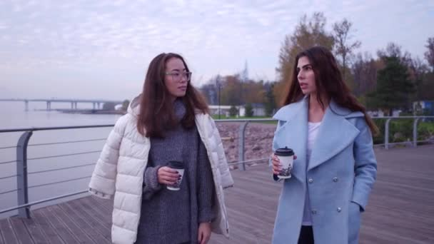 Outdoors fashion portrait of two cheerful girls, asian and arabian drinking coffee. Walking on the embankment.