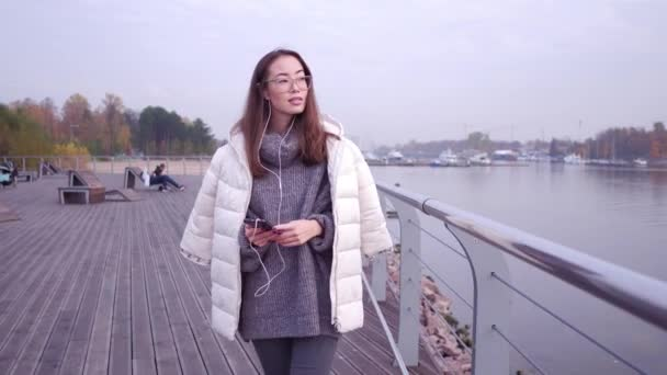 Young asian woman using smart phone standing on sea coast of embankment. Female dressed in grey sweater and white jacket holding mobile device on background of open water, close-up.