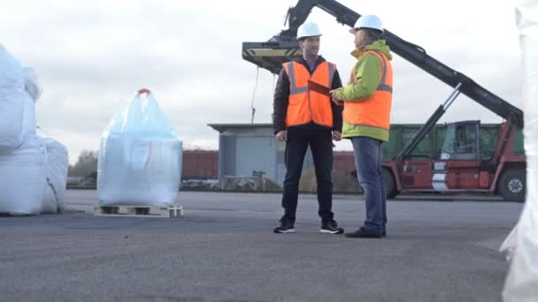 Two engineers wearing hardhats talking together while standing on a large commercial trainyard tracking inventory