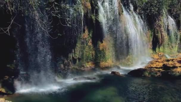 AERIAL.Camera moving from waterfall to Young traveler woman with Red Backpack travel into amazing beautiful waterfall in tropical rain forest