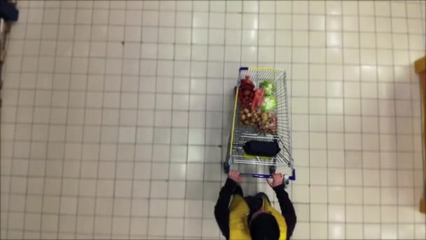 A Shopper Pushes a Trolley along a Supermarket Aisle - View from the top.