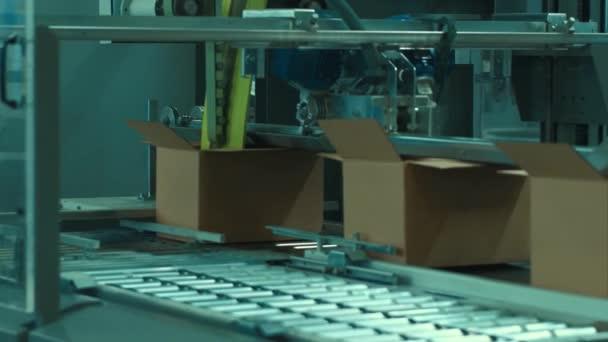 Cardboard packing machine, on conveyor belt.