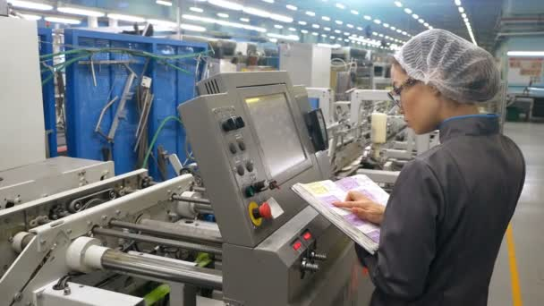 On High Tech Factory Asian Woman Engineer Uses instruction book for Programing Pick and Place Electronic Machinery.