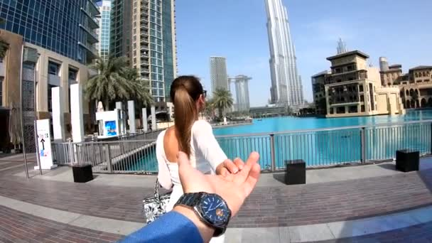 Luxury travel vacation woman holding hand of husband following her, view from behind. Woman looking at view on Dubai famous travel destination.