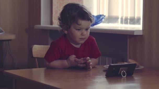 Zapnete tento jeden. Rozkošný snímek ze dvou různých věku děti sedí vedle sebe a zaměřuje svou pozornost na obrazovku smartphone zároveň obě poslech hudby doma.