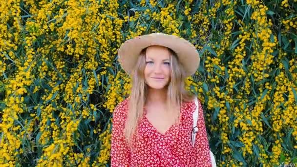 Blond girl in a straw hat on a background of yellow flowers. Sunny day and beautiful nature. Fashion concept.