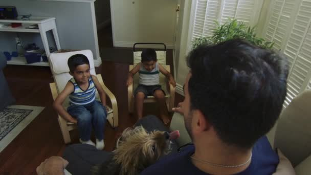 Slow motion of kids jumping on dad's arms while he sits with a dog on his lap