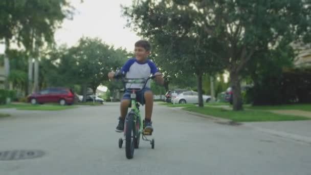 Zpomaleně kid jízdní kolo přes čtvrť
