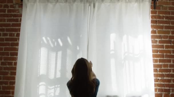Slow motion of woman opening white curtains by brick walls and looking out