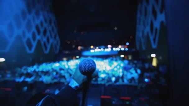 Énekesnő kezét, megragadta a mikrofont, miközben a színpadon egy állványra tömeg előtt