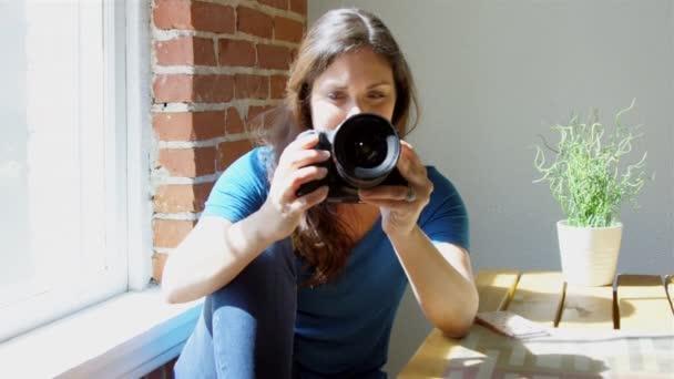 Zpomalený pohyb ženy kontrolu fotografií na svůj fotoaparát a usmívá se
