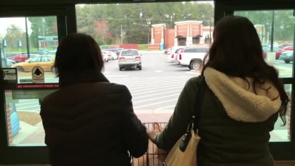 Two women pushing a shopping cart as they exit store
