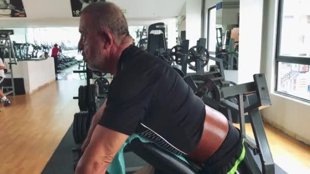 Profil záběr starší muž dělá zpět cvičení na kryté tělocvičně pomocí vah