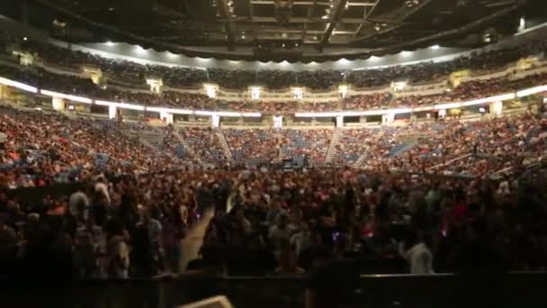 Shot of unrecognizable audience at a full coliseum before a concert. People sitting down and others walking around