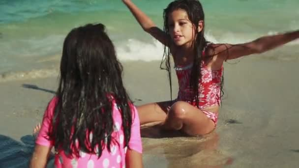 Great shot of two little girls/sisters sitting by the ocean playing with sand.