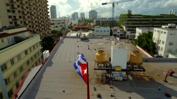 Daytime close-up shot of a Cuban flag, then aerial view of Miami Beach area in Florida