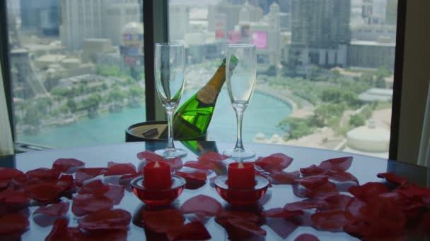 Champagner und Gläser auf einem Tisch mit roten Blütenblättern vor toller Aussicht