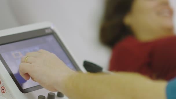 Lassú mozgás a gép és mosolygós terhes nő kap egy ultrahang
