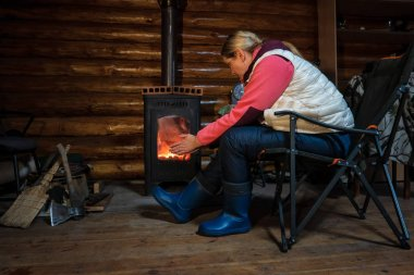 A woman in clothes for outdoor activities warms her hands by the stove of a village house. A fire is burning in a small cast iron stove. There is a folding chair, an ax, a broom and a wall of logs.