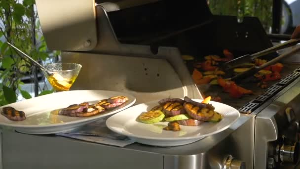 Cook lay out on plates with help of forceps various vegetables such as eggplant, pepper, zucchini and mushrooms. Healthy food is cooked on the grill. Man is preparing to serve a deliciously cooked