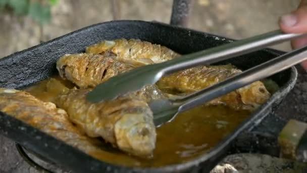 Kochen Fisch in Öl in einer Pfanne und Grill. Braten von Fisch unter freiem Himmel. Professionelles catering. Knusprige Köstlichkeiten. Kochen Sie mit Zange nimmt das fertige Gericht auf dem Teller