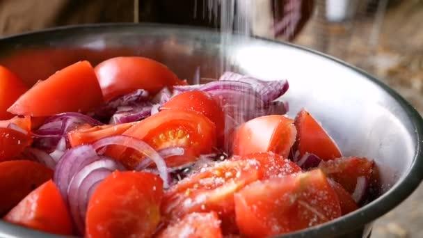 Salad of sliced tomato and blue onion sprinkled with large sea salt. Healthy food vitamins vegetables.