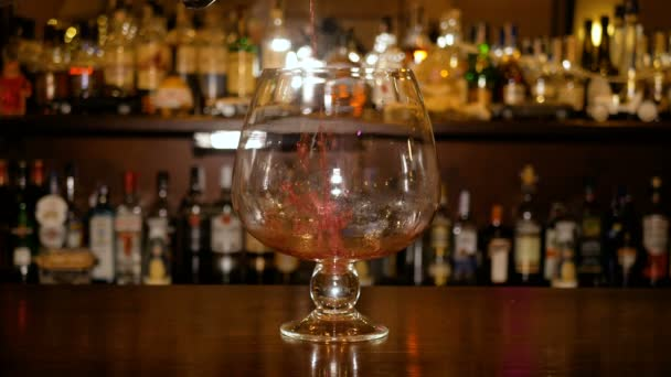 Hot wine is poured into a large glass cup on the background of a bar cabinet with bottles. Cooking Mulled Wine.