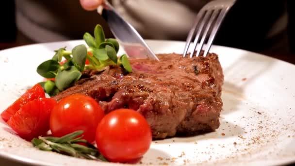 Kuchařka vyjme a předvádí čerstvě připravený masový steak.