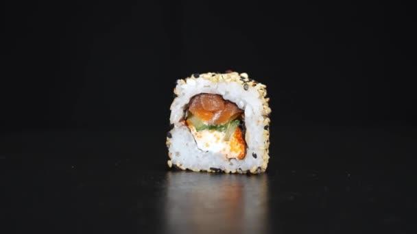 A sushi tekercs fekete alapon forog. Közelkép fotózás. Philadelphia sajt és lazac japán ételekben.