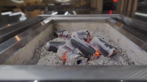 Přikryjte gril žhavým uhlím mřížkou. Detailní záběr. Stůl v grilovací restauraci.
